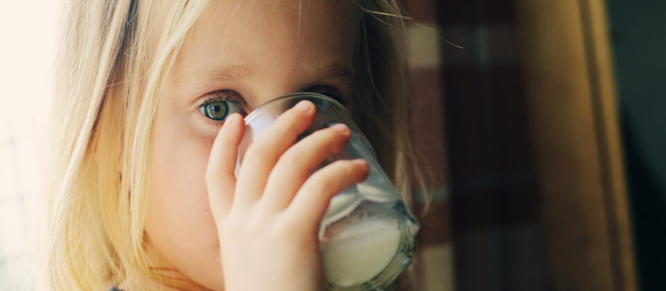 5 years old girl holding glass of milk